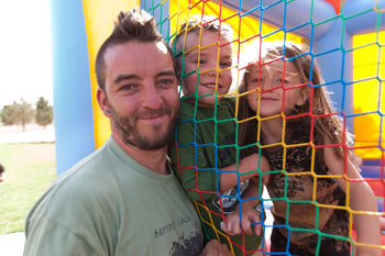 REEL FATHERS-Father's Day Fiesta: Father, young son and daughter having fun by jumpy house